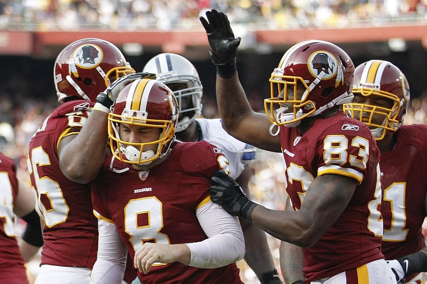 Washington Redskins quarterback Rex Grossman is congratulated by teammates after scoring a touchdown on a quarterback keeper during the first half against the Dallas Cowboys in Landover, Md., on Sunday, Nov. 20, 2011. (AP Photo/Evan Vucci)
