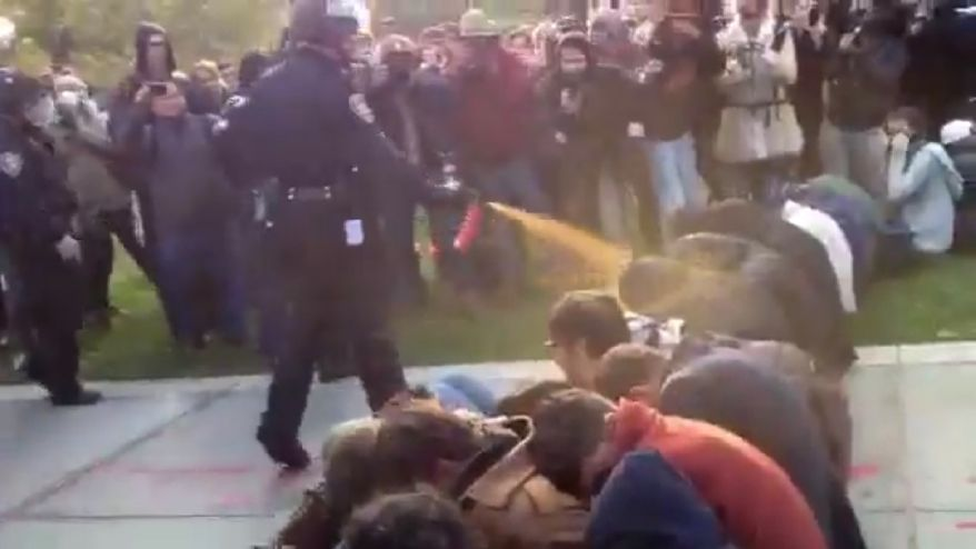 In this image made from video, a police officer uses pepper spray as he walks down a line of Occupy demonstrators sitting on the ground at the University of California, Davis on Friday, Nov. 18, 2011. (AP Photo/Thomas K. Fowler)