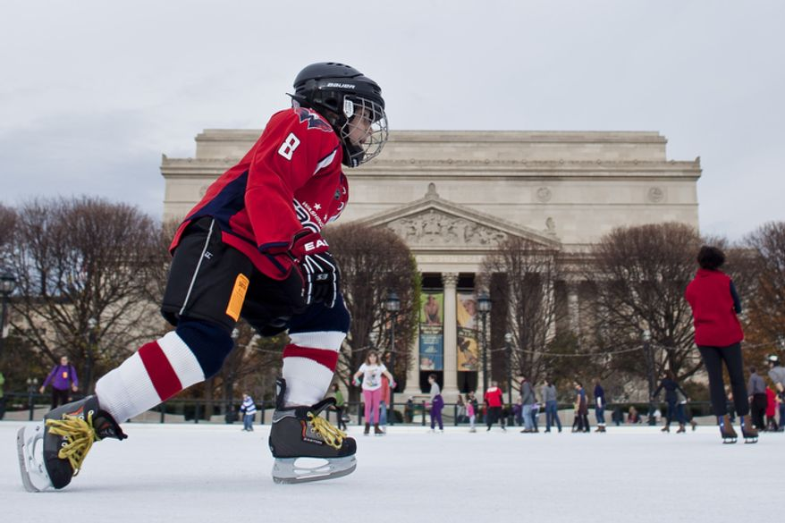 Lukas Jordana, 7, of Sterling, Va., dressed as the Capitols' Alex Ovechkin, skates past the National Archives during the opening weekend of the National Gallery of Art sculpture garden ice rink in Washington, D.C. on Nov. 20, 2011.(T.J. Kirkpatrick/ The Washington Times)