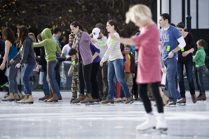 Skaters pour out on to the ice after a pass of the Zamboni during the opening weekend of the National Gallery of Art sculpture garden ice rink. (T.J. Kirkpatrick/ The Washington Times)