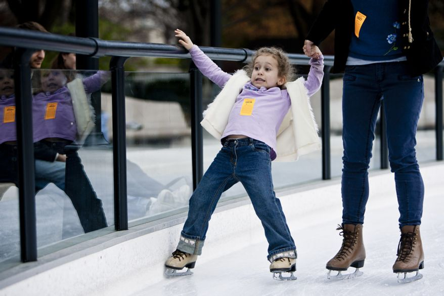 Lilla Harrigan, 5, holds tight to her mother Cheyenne Bsaies, of Fairfax, Va., as they skate during the opening weekend of the National Gallery of Art sculpture garden ice rink.(T.J. Kirkpatrick/ The Washington Times)