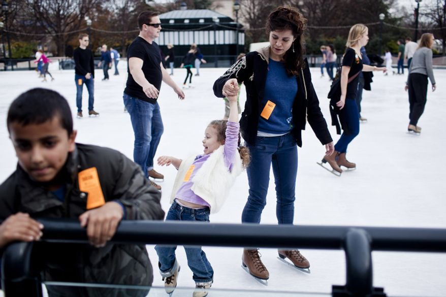 Lilla Harrigan, 5, at center, holds tight to her mother Cheyenne Bsaies, of Fairfax, Va., as they skate. (T.J. Kirkpatrick/ The Washington Times)