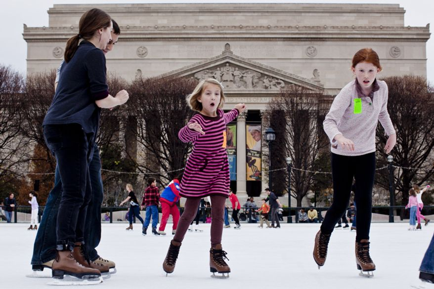 Nora O'Prey, 10, of Bethesda, Md., right, races her cousin Kiera Walker, 6, visiting from San Francisco, Calif., across the rink during the opening weekend of the National Gallery of Art sculpture garden ice rink.(T.J. Kirkpatrick/ The Washington Times)