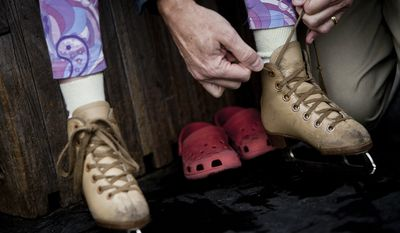 David Diggs, of Washington, D.C., ties up the skates for his daughter, Josie. (T.J. Kirkpatrick/ The Washington Times)