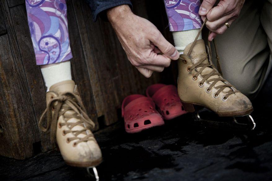 David Diggs, of Washington, D.C., ties up the skates for his daughter, Josie. (T.J. Kirkpatrick/ The Washington Times)