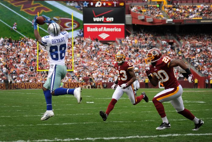 Dallas Cowboys wide receiver Dez Bryant (88) hauls in a 22-yard touchdown reception in front of Washington Redskins free safety Oshiomogho Atogwe (20) and cornerback DeAngelo Hall (23). (Andrew Harnik/The Washington Times)