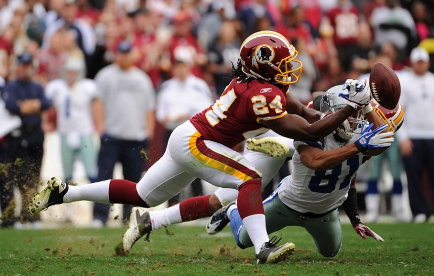 Washington Redskins defensive back DeJon Gomes (24) breaks up a pass intended for Dallas Cowboys wide receiver Laurent Robinson (81) but is called for pass interference during second quarter action. (Andrew Harnik/The Washington Times)
