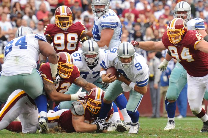 Dallas Cowboys quarterback Tony Romo (9) is sacked by Washington Redskins nose tackle Chris Neild (bottom) and Adam Carriker (94) for a 4-yard loss during second quarter action. (Andrew Harnik/The Washington Times)