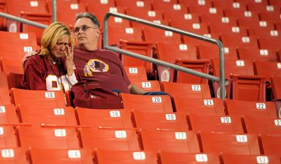 Melanie Etter (L)  and Chris Clarke, from Glen Burnie, Md., sit in the stands after a 27-24 Redskins loss to Dallas in overtime at FedEx Field in Landover, Md., on Sunday, November 20, 2011. (Andrew Harnik/The Washington Times)