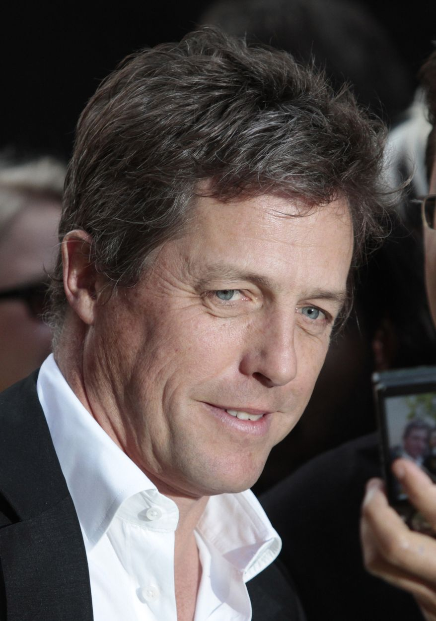 ** FILE ** In this Monday, May 9, 2011, file photo of British actor Hugh Grant, as he poses with fans as he arrives for the European premiere of the 'Fire in Babylon' film at a cinema in London. (AP Photo/Lefteris Pitarakis, File)
