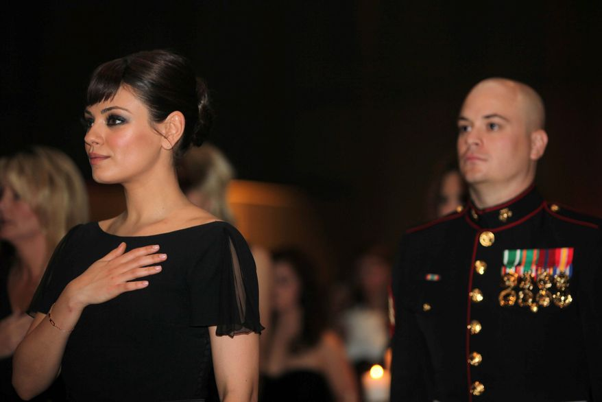 Actress Mila Kunis rests her hand over her heart during the playing of the National Athem at the 236th Marine Corps birthday ball in Greenville, N.C., on Friday. Her date, Sgt. Scott Moore, is behind her. (Associated Press)