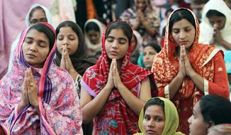 People from the Pakistani Christian community in Karachi, Pakistan, attend a Sunday service at the new St. Peter's church. The domed, three-story building towers over the sprawling slum it serves and is the largest yet in the violent, Muslim country. (Associated Press)