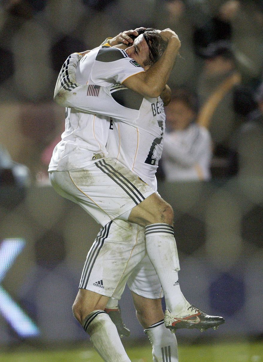 Los Angeles Galaxy forward Landon Donovan, left, jumps into the arms of midfielder David Beckham after they won the MLS Cup championship soccer match against the Houston Dynamo, Sunday, Nov. 20, 2011, in Carson, Calif. The Galaxy won 1-0. (AP Photo/Bret Hartman)