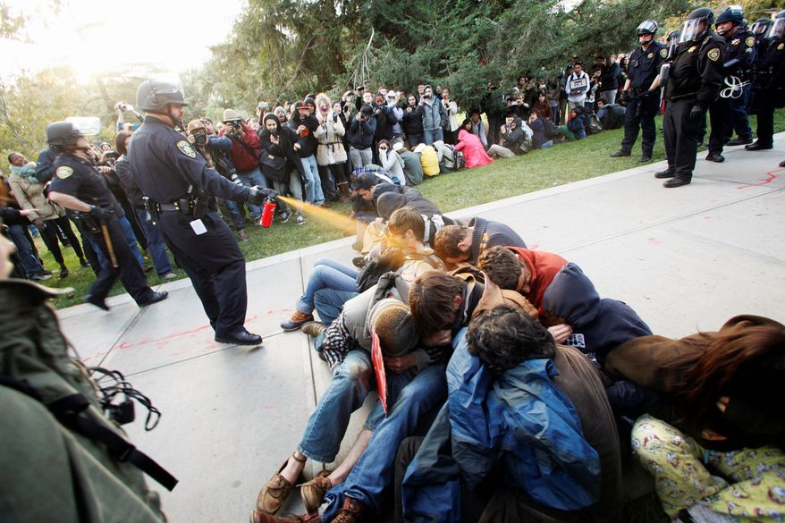 A University of California, Davis police officer uses pepper spray to move Occupy UC Davis protesters while blocking their exit from the school's quad in Davis, Calif., on Friday. Two were hospitalized. The pictures of the incident went viral over the weekend, and UC Davis authorities apologized Monday. (Associated Press)