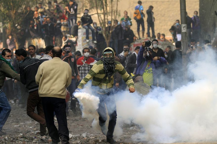 A protester runs to throw a tear gas canister away during clashes with the Egyptian riot police near Tahrir square in Cairo, Egypt, Tuesday, Nov. 22, 2011. (AP Photo/Khalil Hamra)