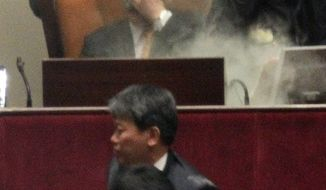 Rep. Kim Seon-dong of the opposition Democratic Labor Party (center bottom) is blocked Nov. 22, 2011, by a security officer as National Assembly Vice Speaker Chung Eui-hwa (center seated) covers his face after Kim exploded tear gas to try to block the passage of a bill on ratification of a South Korea-U.S. free trade agreement at the National Assembly in Seoul. (Associated Press)