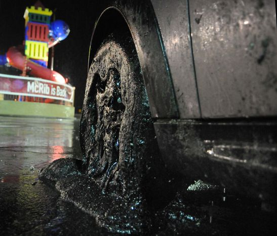A car with its wheels covered in driveway sealant sits in a parking lot in Harmar, Pa., after exiting the Pennsylvania Turnpike Tuesday night, Nov. 22, 2011. (AP Photo/Valley News Dispatch, Erica Hilliard)
