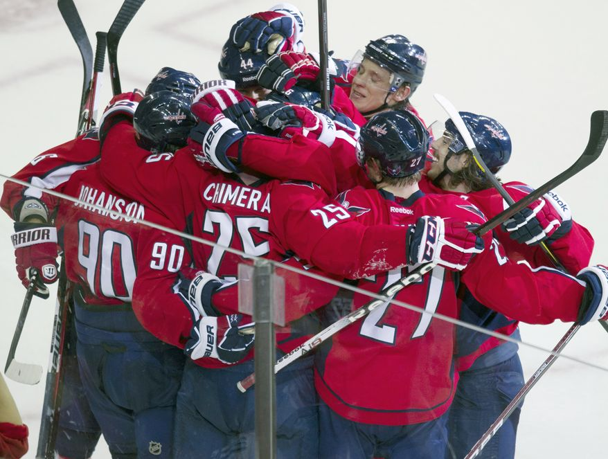 Washington Capitals left winger Jason Chimera is rushed by teammates after scoring the game-winning goal against the Winnipeg Jets in overtime Wednesday, Nov. 23, 2011 in Washington. The Caps won 4-3. (AP Photo/Evan Vucci)