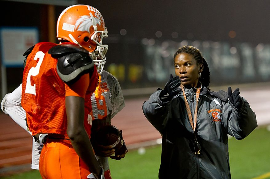 Coolidge High School Football Coach Natalie Randolph gives direction to Dayon Pratt, left, during practice in preparation for the Turkey Bowl, Washington, DC, Monday, November 21, 2011. (Andrew Harnik/The Washington Times)