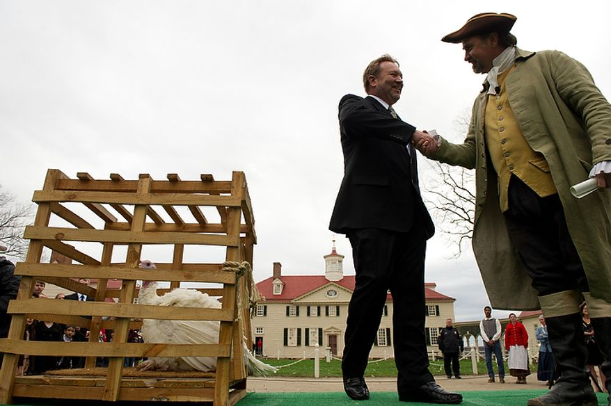 Richard Huisinga, chairman of the National Turkey Federation, shakes hands with Tom Plott, who plays George Washington's farm manager James Anderson at Mount Vernon in Virginia, as Liberty, the turkey pardoned by President Obama, is welcomed to Mount Vernon on Nov. 23, 2011. (Andrew Harnik/The Washington Times)