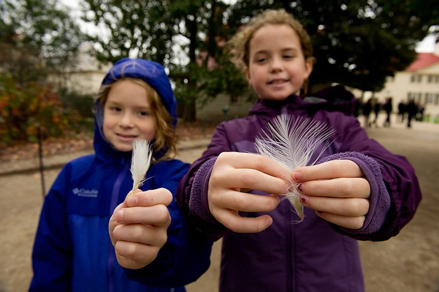 Sarah Frances Gilroy (left), of Birmingham, Ala., and her sister Caroline show the feathers they picked up from Liberty, the turkey pardoned by President Obama, as it was welcomed to Mount Vernon in Virginia on Nov. 23, 2011. (Andrew Harnik/The Washington Times)