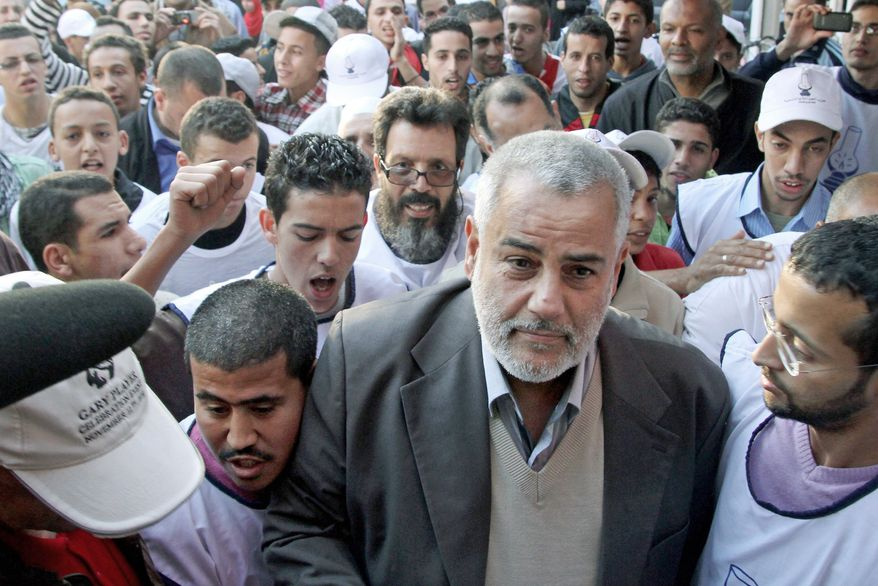 Abdelilah Benkirane, the secretary-general of Morocco's opposition Islamist Justice and Development Party (front center), arrives for an election rally ahead of upcoming nationwide legislative elections in Sale, Morocco, earlier this month. Mr. Benkirane has high hopes for his party. (Associated Press)