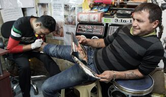Saad Saif, 25, gets a tattoo done by Mohammed Abass, 28, in Baghdad. He is one of many young Iraqis who have adopted the ways of some of the U.S. soldiers who have been in their country for eight years. For them, rap music, tattoos and American slang are part of what the departing forces are leaving behind. (Associated Press)