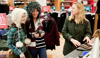 Gina Youngman (right) of New Canaan, Conn., reacts as daughter Sarah (left), 15, and friend Celina Sprague, of the District, try on hats at the Gap store on Thanksgiving Day in the Georgetown section of the District. Many retailers were open on Thanksgiving. (T.J. Kirkpatrick/The Washington Times)