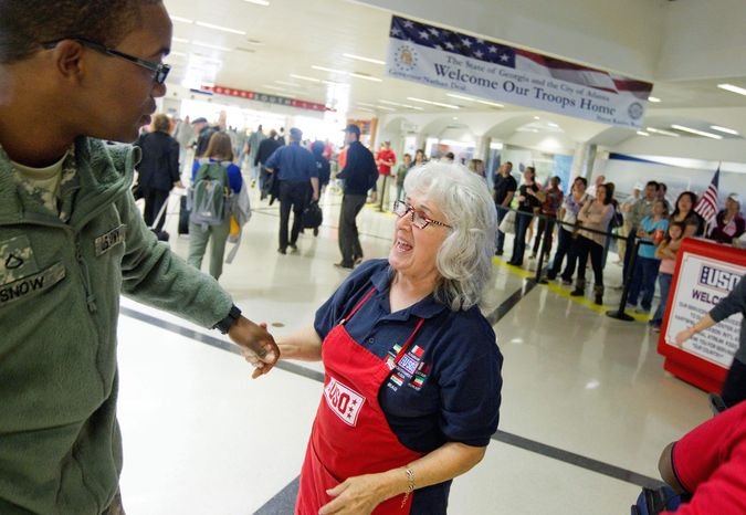 """USO volunteer Pat Solomon of Sandy Springs, Ga., greets Army Pfc. Damien Snow, 20, of Rochester, N.Y., as he returns to his base at Fort Benning, Ga., at Hartsfield-Jackson International Airport in Atlanta on Tuesday. """"I want to tell them how I feel, and how the USO feels. It's amazing, what they do for the world,"""" Mrs. Solomon says. (Associated Press)"""