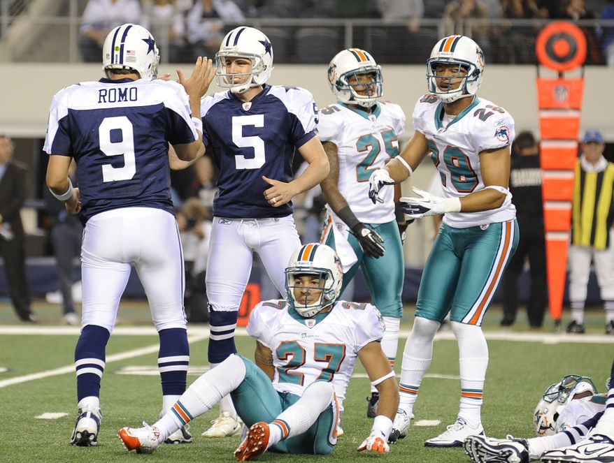 Dallas Cowboys quarterback Tony Romo and kicker Dan Bailey celebrate Bailey's game-winning field goal as Miami Dolphins cornerback Jimmy Wilson, Will Allen  and Nolan Carroll look on Thursday, Nov. 24, 2011, in Arlington, Texas. The Cowboys won 20-19. (AP Photo/Matt Strasen)