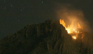 A brush fire burns at the scene of an aircraft that crashed in the Superstition Mountains in Apache Junction, Ariz., on Wednesday, Nov. 23, 2011. The small plane with three adults and three children on board crashed into the Superstition Mountains east of Phoenix on Wednesday, and there was no sign of survivors, authorities said. (AP Photo/Tim Hacker East Valley Tribune)