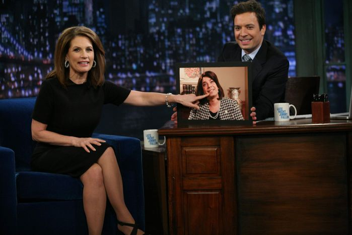 """In this image released by NBC, Republican presidential candidate Michele Bachmann, of Minnesota, left, points to a photo of host Jimmy Fallon, dressed as Bachmann, during a visit to """"Late Night with Jimmy Fallon,"""" that aired early Tuesday, Nov. 22, 2011, in New York. (AP Photo/NBC, Lloyd Bishop)"""