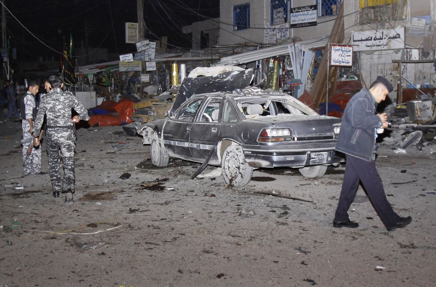 Security forces inspect the scene of a bomb attack in Basra, 340 miles (550 kilometers) southeast of Baghdad, Iraq, Thursday, Nov. 24, 2011. Three bombs went off in a popular open-air market Thursday evening, killing and wounding scores of people, police said. (AP Photo/Nabil al-Jurani)