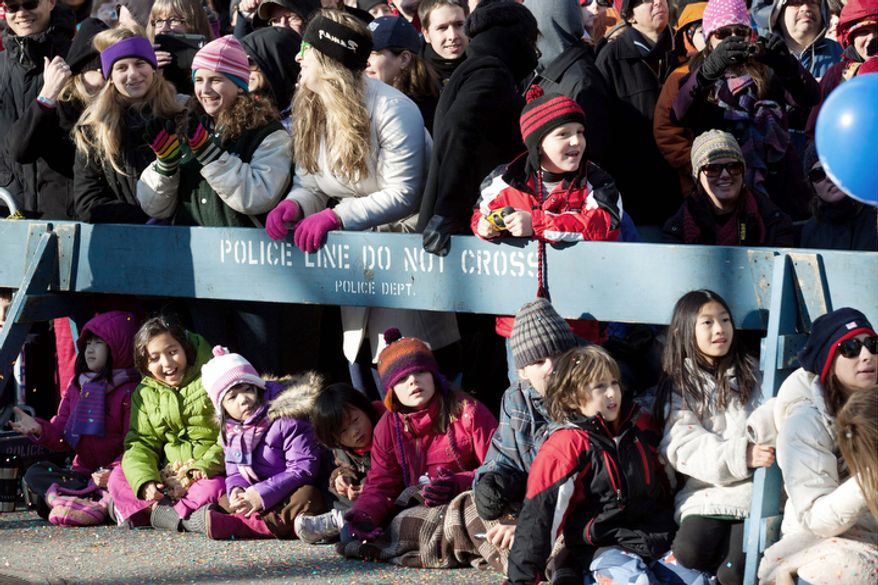 Spectators watch the Macy's Thanksgiving Day Parade from behind police barricades. (AP Photo/John Minchillo)