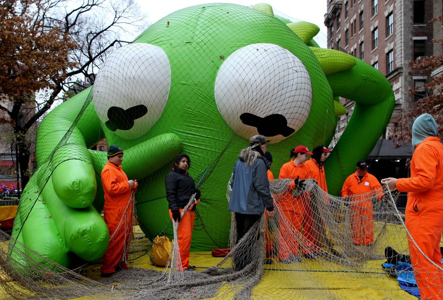 The Kermit the Frog balloon seems to reach out toward balloon handlers with Macy's department store's 85th annual Macy's Thanksgiving Day Parade as they work on another one of 15 giant helium balloons and 44 novelty and specialty balloons Wednesday, Nov. 23, 2011, that will be featured in Thursday's parade in New York. (AP Photo/Craig Ruttle)