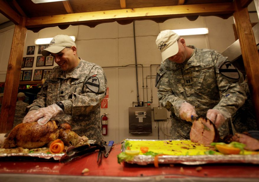 U.S. soldiers serve food for the last Thanksgiving meal at Contingency Operating Site Echo, in Diwaniyah, 120 kilometers (80 miles) south of Baghdad, Iraq, Thursday, Nov. 24, 2011. The U.S. has promised to withdraw from Iraq by the end of the year as required by a 2008 security agreement between Washington and Baghdad. A little less than 20,000 U.S. troops are scheduled to clear out along with their equipment. (AP Photo/Khalid Mohammed)