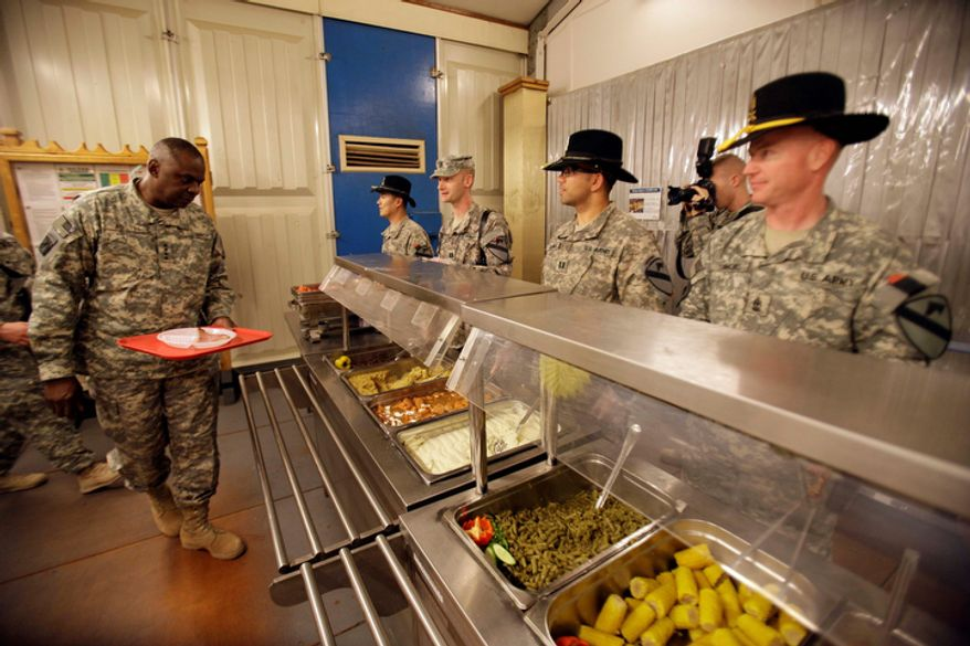 U.S. soldiers serve Thanksgiving meal for Gen. Lloyd Austin, left, the top U.S. commander in Iraq at Contingency Operating Site Echo, in Diwaniyah, 120 kilometers (80 miles) south of Baghdad, Iraq, Thursday, Nov. 24, 2011. The U.S. has promised to withdraw from Iraq by the end of the year as required by a 2008 security agreement between Washington and Baghdad. A little less than 20,000 U.S. troops are scheduled to clear out along with their equipment. (AP Photo/Khalid Mohammed)