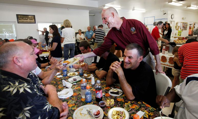 Florida Gov. Rick Scott, center, helps serve Thanksgiving dinner to guests at St. Matthew's House homeless shelter in Naples, Fla., on Thursday, Nov. 24, 2011. St. Matthew's House officials estimate feeding nearly 7,000 people for the Thanksgiving holiday through their turkey and grocery give-away and the sit-down dinner on Thursday afternoon. (AP Photo/Naples Daily News, Tristan Spinski)  FORT MYERS OUT; MAGS OUT; NO ADS; MANDATORY CREDIT