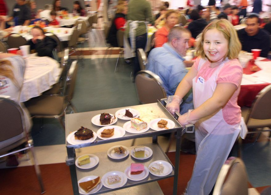 Volunteer Emmy Ridings, 8, wheels a dessert cart through the Salvation Army Community Thanksgiving dinner at the First Presbyterian Church in Winchester, Va., Thursday Nov. 24, 2011.  Nearly 1,000 meals were served during the dinner. (AP Photo/The Winchester Star, Scott Mason)