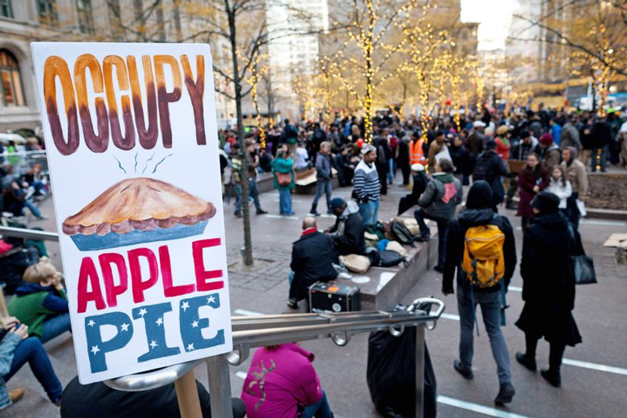 Occupy Wall Street protestors host Thanksgiving dinner in Zuccotti park, Thursday, Nov. 24, 2011, in New York. Protestors used the holiday to give thanks alongside strangers at outdoor Occupy encampments nationwide, serving turkey or donating their time in solidarity with the anti-Wall Street movement. (AP Photo/John Minchillo)