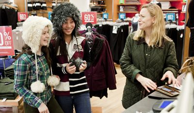 Gina Youngman, right, of New Canaan, Conn., reacts as her daughter Sarah, 15, from left, and friend Celina Sprague, of Washington, D.C., model hats at the Gap's Georgetown store on Thanksgiving day in Washington, D.C. on Nov. 24, 2011.