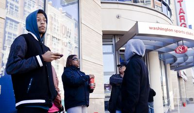 Mason Binion, of Washington, D.C., at left and Tasha Johnson, of Washington, center, wait in line with other shoppers along 14th Street NW for the midnight opening at the DC USA Shopping Center in Columbia Heights on Thanksgiving day in Washington, D.C. on Nov. 24, 2011.(T.J. Kirkpatrick/ The Washington Times)