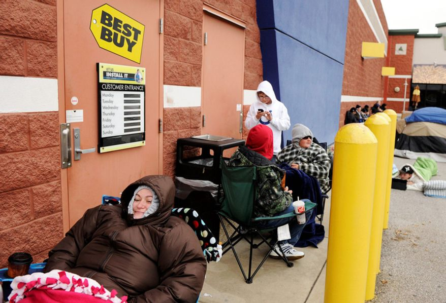 Nicole Bass, left, tries to stay warm while waiting outside of Best Buy in Evansville, Ind., on Thursday, Nov.  24, 2011.  Bass got to the store about 11:30 a.m. on Thursday and estimates that she is about 25th in line. She's hoping to get a 42-inch television for $200 when the store opens at midnight. This weekend, many stores will for the first time use midnight openings along with the usual bevy of deals as they try to lure consumers, whose appetite for good-buys has been increasing since the Great Recession. (AP Photo/Evansville Courier & Press, Molly Bartels )