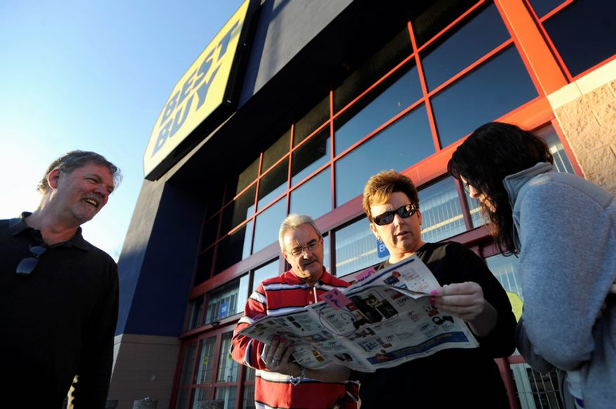 From left, Mark Pugh, Frankie and Pam Davis, and Jamie Pugh look over the discounts that await them when Best Buy's doors open at midnight, at the Wards Crossing Shopping Center in Lynchburg, Va.,  Thursday, Nov. 24, 2011. Mark Pugh was first in line at Best Buy, arriving at 5:15 a.m., beating the next arrivals by about 15 minutes. This weekend, many stores will for the first time use midnight openings along with the usual bevy of deals as they try to lure consumers, whose appetite for good-buys has been increasing since the Great Recession. (AP Photo/News & Daily Advance, Parker Michels-Boyce)