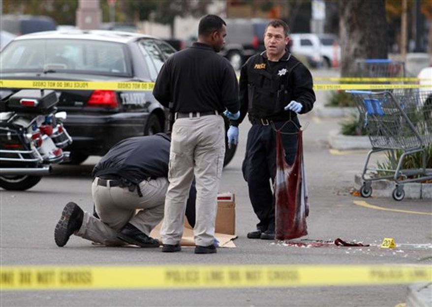 A San Leandro police officer, right, holds a bloody shirt as evidence is gathered at the scene of a shooting at Wal-Mart on Hesperian Boulevard, Friday, Nov. 25, 2011, in San Leandro, Calif. Gunfire rang out about 1:50 a.m. and a man was shot in a robbery attempt. Despite major injuries, police said he was in stable condition. (AP Photo/Bay Area News Group, Jane Tyska