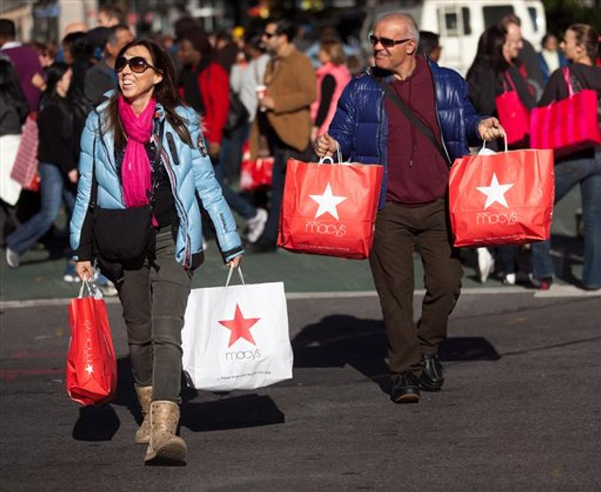 Consumers lug their bags through Herald Square during the busiest shopping day of the year, Friday, Nov. 25, 2011, in New York. Some of the nation's major chain stores opened late Thursday, competing for holiday shoppers on the notoriously busy Black Friday to kick off a period that is crucial for the retail industry. (AP Photo/John Minchillo)