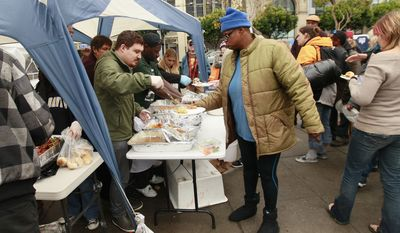 Occupy San Francisco protesters are served a turkey dinner provided by Glide Memorial Church at Justin Herman Plaza in San Francisco on Nov. 24, 2011. (Associated Press)