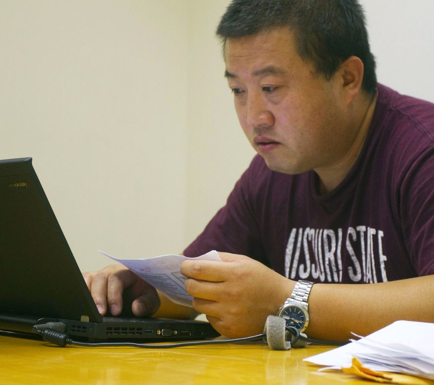 **FILE** Wang Chengdong, a Chinese student in the Executive MBA program, works June 28, 2011, in a library study room at Missouri State University in Springfield, Mo. (Associated Press/The News-Leader)