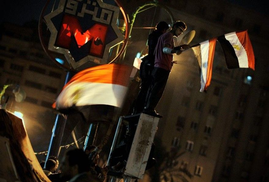 "Egyptians wave national flags while protesting against the country's ruling military council in Cairo's Tahrir Square on Sunday. ""How can we have elections right after so many people have died?"" asked farmer Hemdan El-Ready. (Associated Press)"