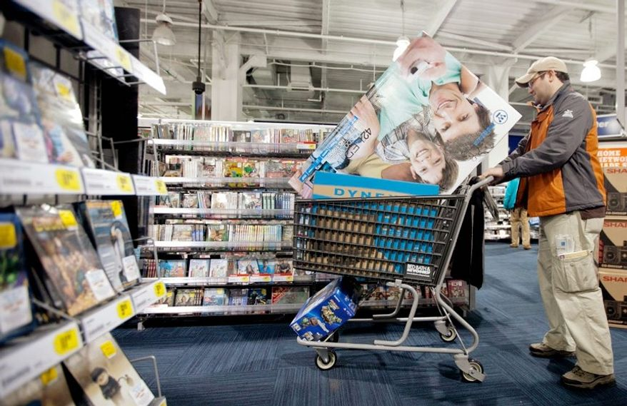 Joel Pizarro fills his cart with several TVs during a midnight doorbuster sale at Best Buy in Columbia Heights on Black Friday. Lines started forming at many stores early on Thanksgiving Day. Total sales at retail stores nationwide on Friday were a record $11.4 billion. (Andrew S. Geraci/The Washington Times)